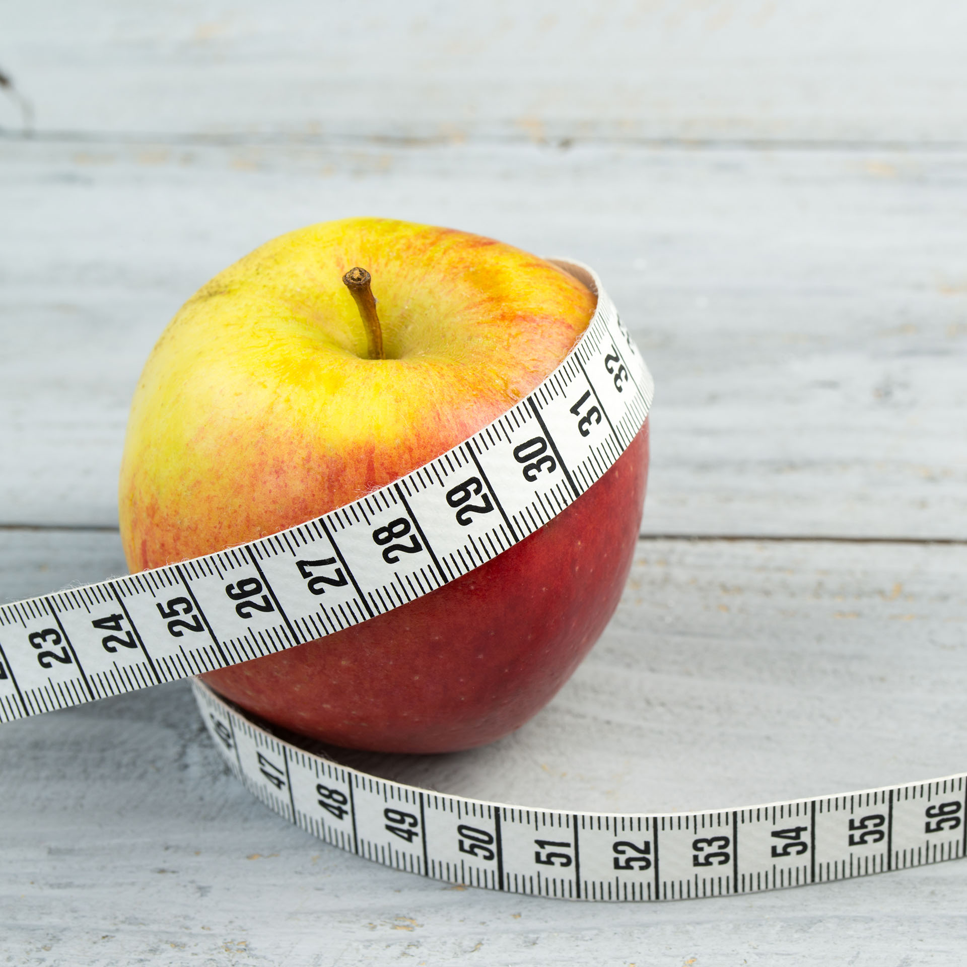 diet fitness, apple with measuring tape wrapped around it