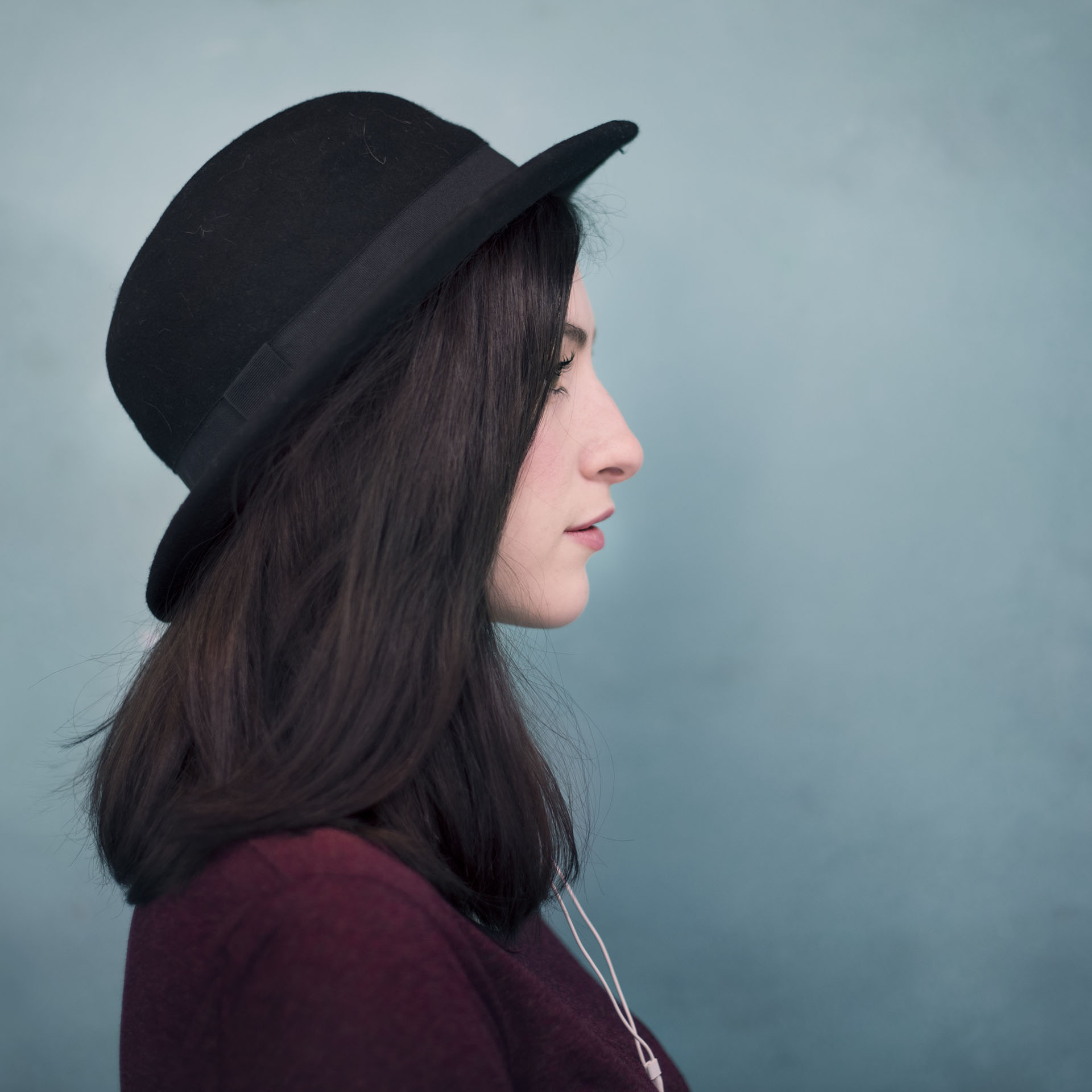 profile, brunette lady in purple shirt and black hat